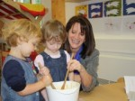 Lynne making a cake with twins at the centre